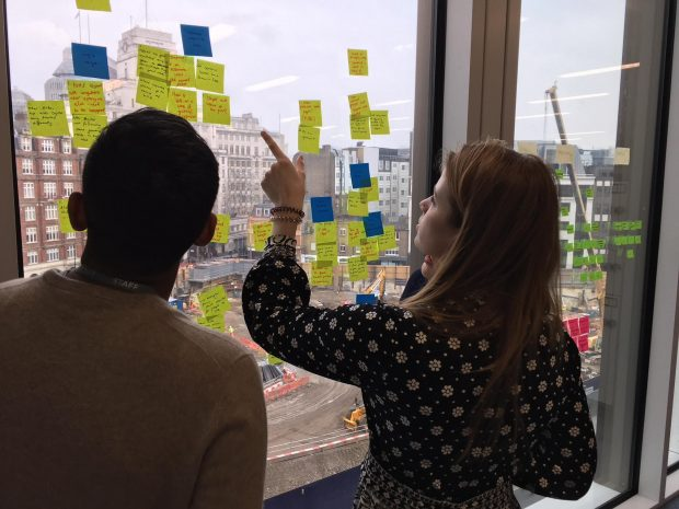 Kassandra reviewing the post its capturing users feedback