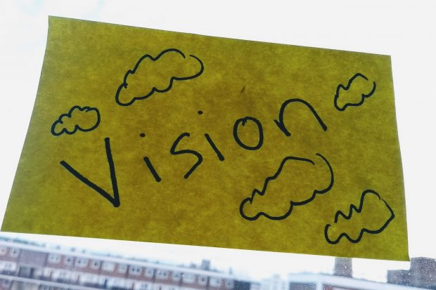 A post it note on a window with vision written on it and clouds around it.