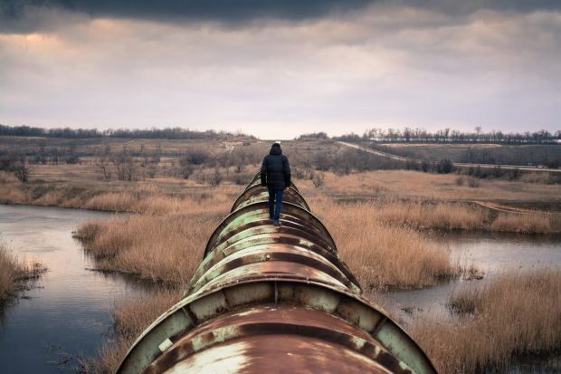 A man walking along a pipeline