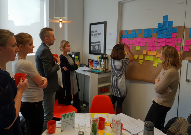 People standing in a meeting room with post-it notes on a board