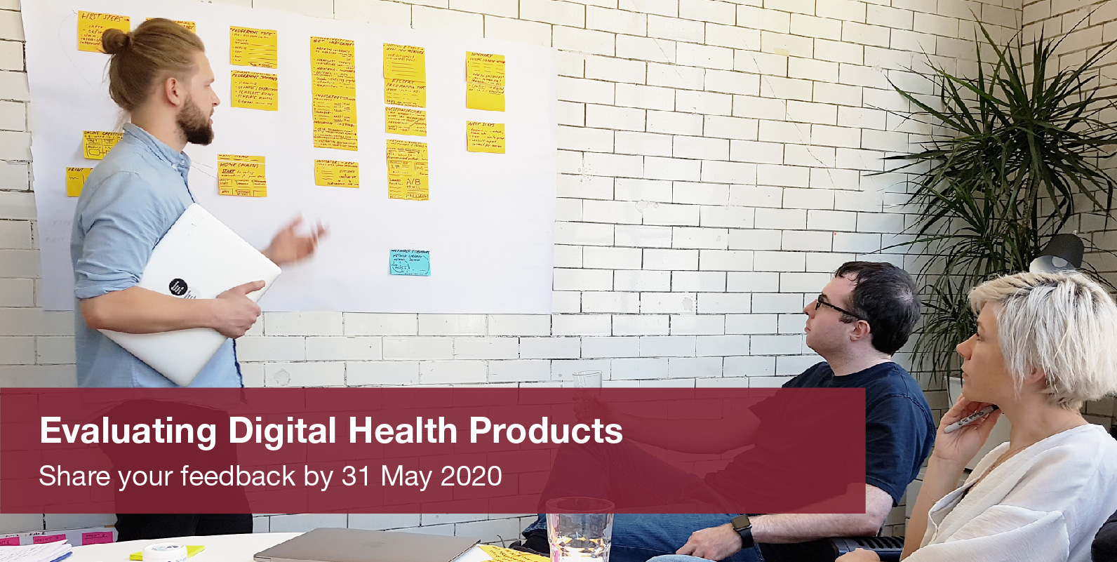 Three people looking at a wall of card. There is banner across the photo that says 'Evaluating Digital Health Products. Share your feedback by 31st May 2020'.